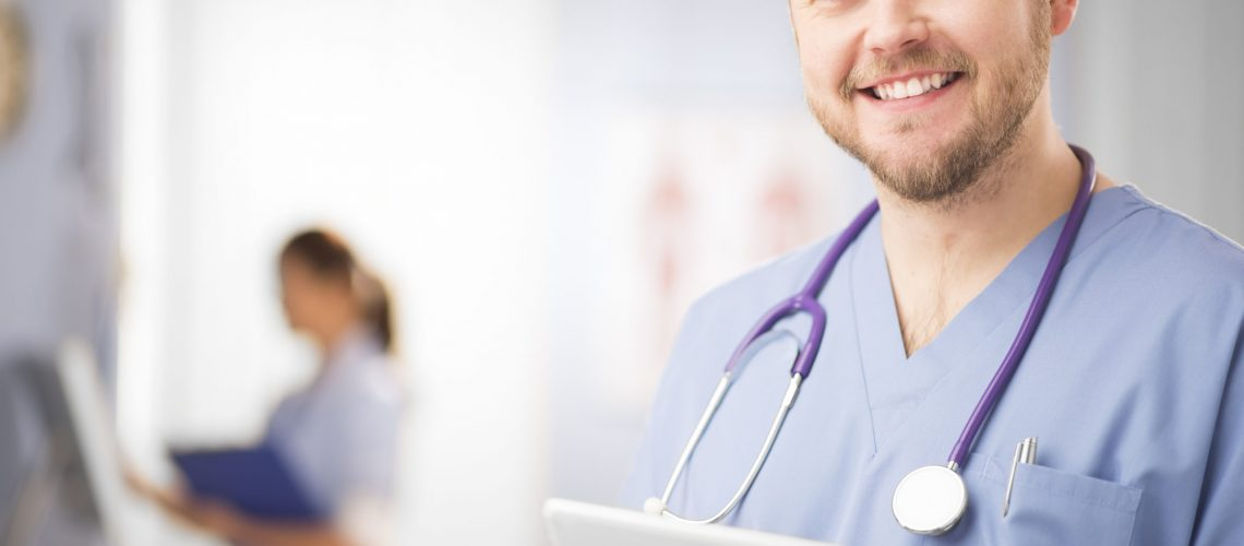 a mid adult male doctor stands with his touchscreen and smiles to camera . He is  dressed in blue medical scrubs , with a stethoscope around his neck , holding a digital tablet .In the background there is a defocussed nurse working at a computer.